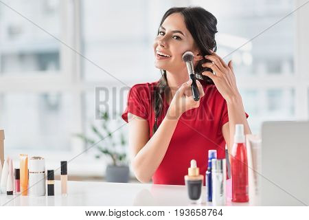 Pretty brunette girl is doing make-up by powder brush. She is sitting at desk and looking forward with joy. Portrait