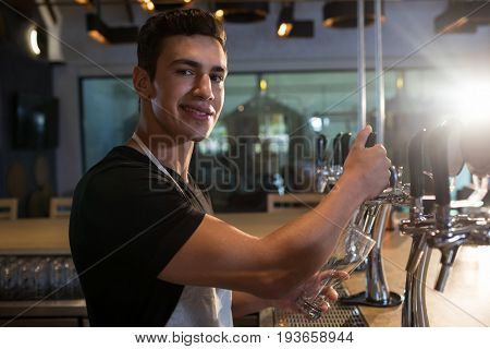 Portrait of bartender pouring beer from tap at bar