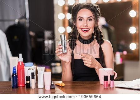 Portrait of excited young woman doing make-up in dressing room. She is pointing finger at moisturizer and smiling