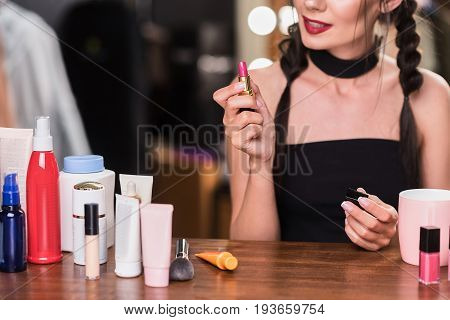 Voluptuous girl is doing make-up in dressing room. She is sitting at desk near other cosmetology. Focus on pink lip gloss