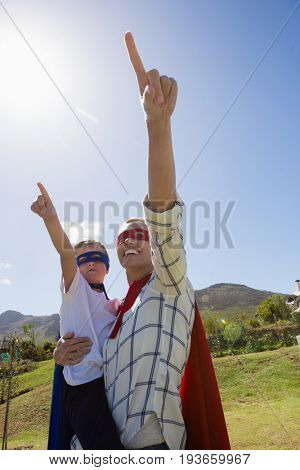 Mother and son pretending to be superhero in the backyard on a sunny day