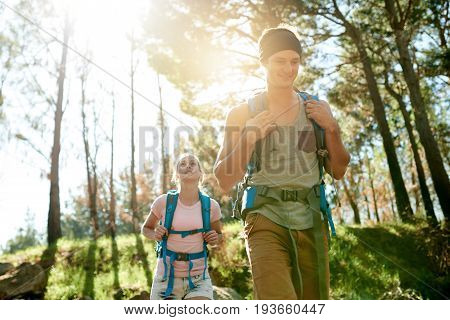Smiling Young Couple Trekking Together Through A Forest