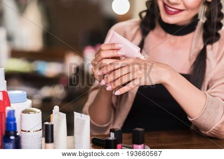 Close up of pretty young woman squeezing foundation on her hand from tube. She is sitting in dressing room and smiling. Focus on her arms