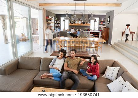 People Sitting On Sofa And Watching TV In Busy Family Household