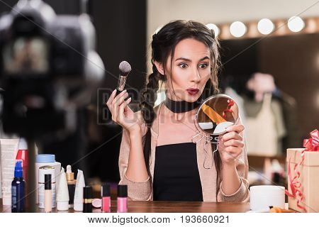 Pretty young woman is doing make-up while sitting in dressing room. She is looking at mirror with surprise and holding blush brush. Camera shooting lady for blog