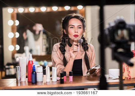 You have chance to be beautiful like me. Portrait of confident young woman pointing make-up brush to camera while leading blog about backstage life