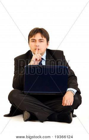 Sitting with laptop on floor businessman holding finger at mouth. Shh gesture isolated on white