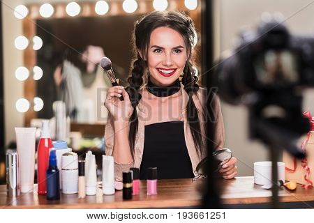 Waist up portrait of sexy female model leading blog about fashion. She is holding powder brush and mirror while looking at camera with pretty smile. Girl is sitting in dressing room