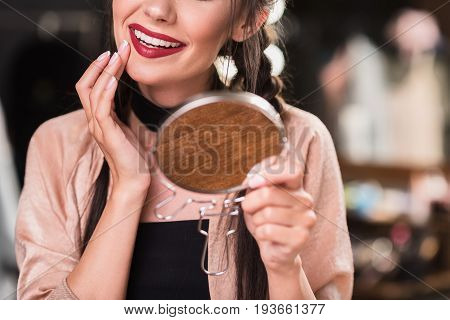 Close up of pretty girl touching her face by hand near lips contour while doing make-up. She is holding mirror and smiling