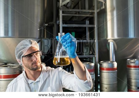 Scientist examining beer in beaker at factory