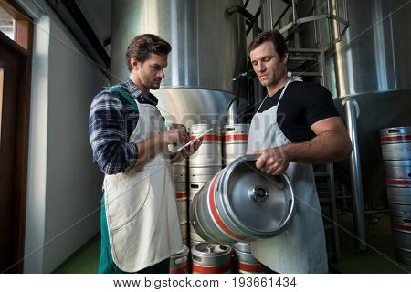 Workers examining kegs at warehouse