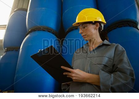 Attentive female worker writing on clipboard in olive factory