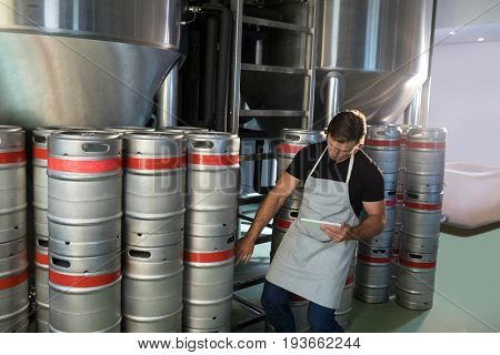 Worker counting kegs at warehouse