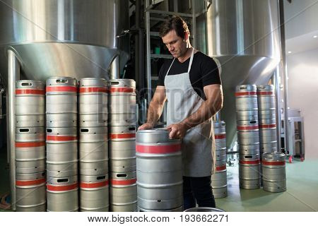 Worker arranging kegs at warehouse