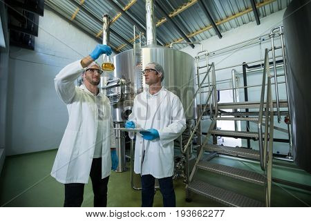 Scientists examining beer in beaker at factory