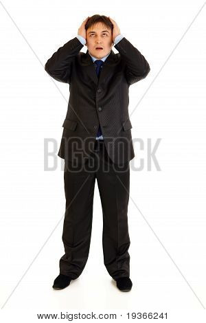 Full length portrait of shocked businessman holding hands near head and looking up isolated on white
