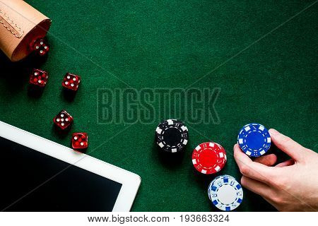 Compulsive gambling. Poker chips and the dice nearby keyboard on green table top view.