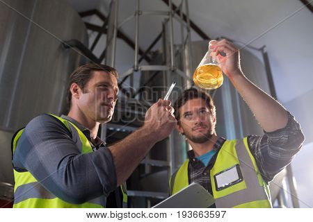 Low angle view of coworkers examining beer in beaker at warehouse