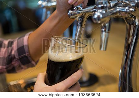Cropped hands of barmaid pouring drink from tap in glass at bar counter