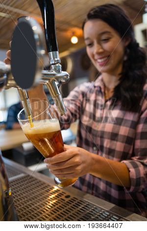 Pretty smiling barmaid pouring beer from tap in glass at restaurant