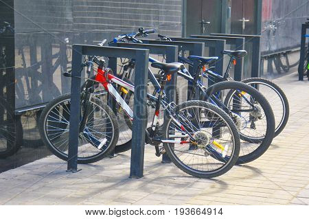 Bicycle parking area with group of colorful bicycles parked together.