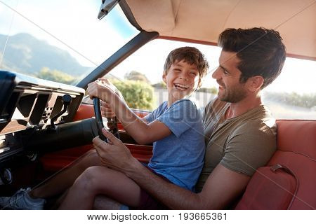 Father Teaching Young Son To Drive Car On Road Trip