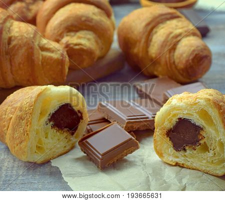 Freshly baked croissants With chocolate filling on the wooden background. Baking/pastry background. Concept for croissants making. Close-up.