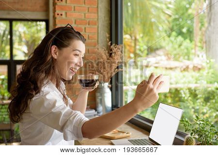 Mixed race lady take self photo while sip hot black coffee and use laptop