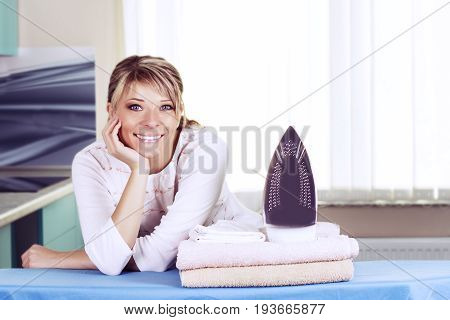 Beautiful young woman is leaning on ironing board looking at camera and smiling while ironing clothes at home
