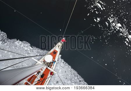 View from the mast on the deck of a ship icebreaker with a team of people. The vessel icebreaker comes out of the water with pieces of ice. A man in red winter clothes is standing on the bow of the ship.