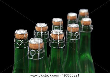 champagne bottles without labels on a black background