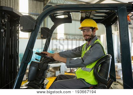 Portrait of smiling worker driving a forklift car in factory