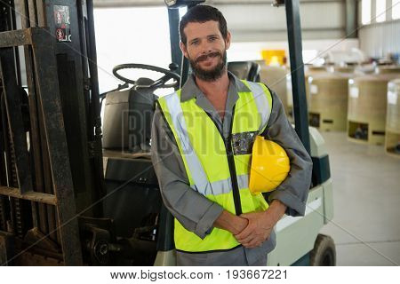 Portrait of smiling worker standing near forklift in factory