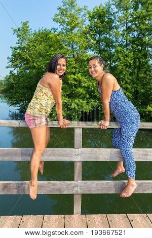 Two young women sitting together on bridge railing at water