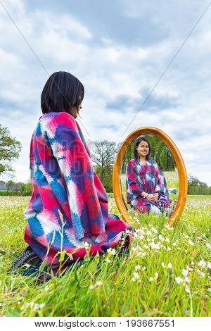 Young colombian woman sits with mirror in flowering pasture