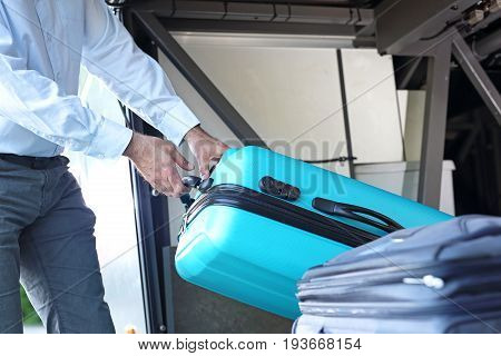Suitcase in the luggage compartment of the tourist coach. The driver removes luggage