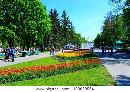 Chernihiv / Ukraine. 06 May 2017: people walk in the city park with flower beds of tulips wide footpath and fountains.  06 May 2017 in Chernihiv / Ukraine.