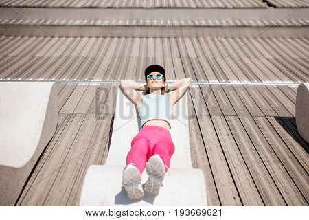 Young woman in sportswear resting after the training lying on the modern sunbed in the city