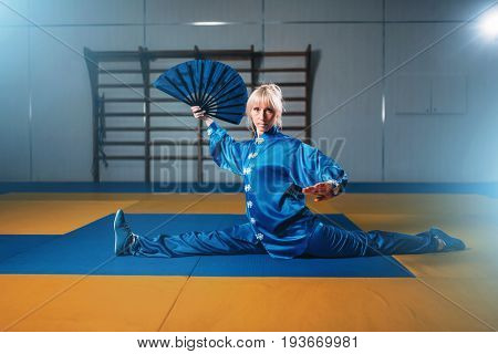 Female wushu master exercise with fan, martial art