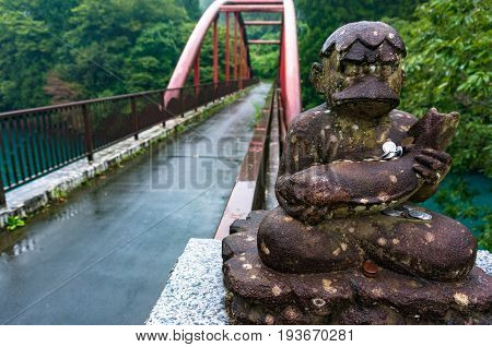 Old Statue Of Idol With Fish And Coin Donations