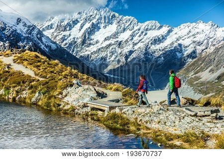 Hiking travel nature hikers in New Zealand mountains. Couple people walking on Sealy Tarns hike trail route with Mount Cook landscape, famous tourist attraction.
