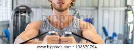 Unrecognizable fitness man strength training in gym doing cable standing fly on tower. Closeup of chest and hands holding handles. Banner panorama crop