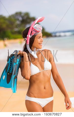 Beach bikini snorkel Asian girl with healthy fit body happy after snorkel swim with fins and diving mask. Summer travel lifestyle watersport leisure activity on holiday vacations.