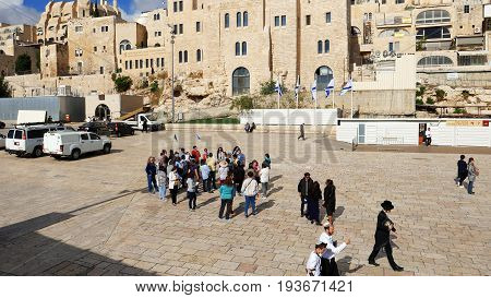 Jerusalem, Israel - May 21, 2017: Group of tourists with guide going to visit the Western wall in Jerusalem. Wailing Wall or Kotel is the most sacred place for all jews and christians on the planet.