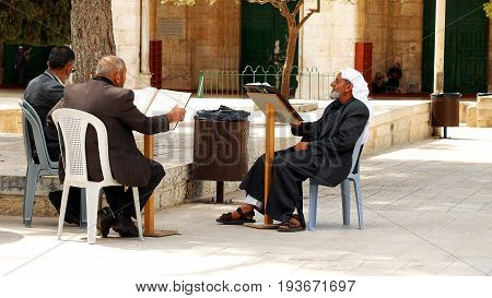 Jerusalem, Israel - May 21, 2017: Three senior Muslims pray and read the Quran at the entrance of Al-Aqsa mosque in Jerusalem or Quddus. Al Aqsa mosque is a sacred place for all muslims and islamic