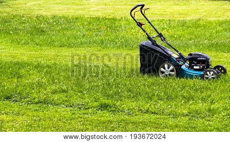 Mowing lawns. Lawn mower on green grass. mower grass equipment. mowing gardener care work tool. close up view. sunny day