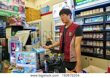 SEOUL, SOUTH KOREA - CIRCA MAY, 2017: worker at 7-Eleven convenience store. 7-Eleven is an international chain of convenience stores.