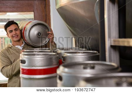 Portrait of smiling male worker carrying keg at warehouse