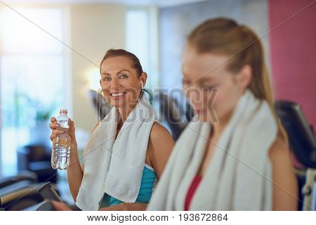 Healthy Middle-aged Woman Drinking Water In A Gym