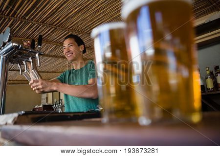 Close-up of beer glasses on counter with bartender looking away at restaurant